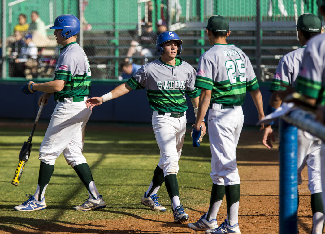 Green Valley's Garrett Nelson, second from left, prepares to high five outfielder Miguel Mariani after Nelson scored in the fifth inning at Green Valley High School on Thursday, April 12, 2018. Gr ...