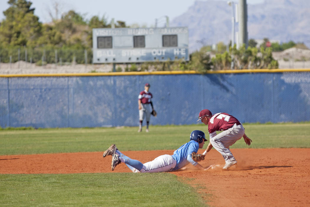 Centennial High School's Zack Simon (3) lands safely to second as Cimarron-Memorial High School's Andrew Johnson (3) attempts to tag him out in a game at Centennial High School in Las Vegas, Frid ...