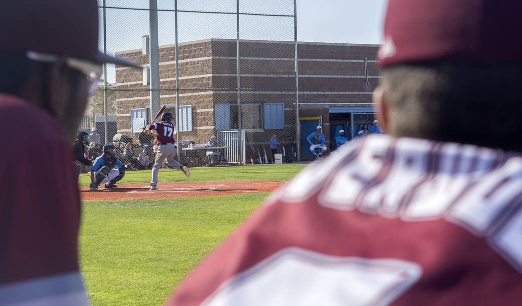 Cimarron-Memorial High School's Trevor Doyle (17) swings for the ball as his teammates watch in a game against Centennial High School at Centennial High School in Las Vegas, Friday, April 13, 2018 ...