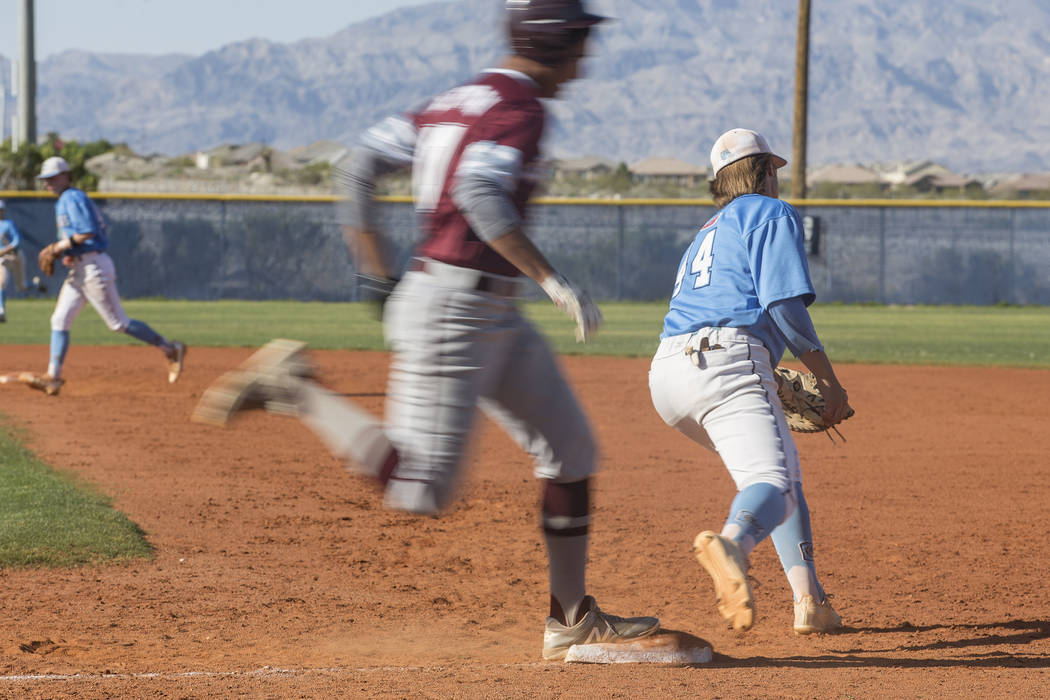 Cimarron-Memorial High School's Seth Hoffman (10) runs through first base as Centennial High School's Kris Bow (44) runs to catch the ball in a game at Centennial High School in Las Vegas, Friday, ...