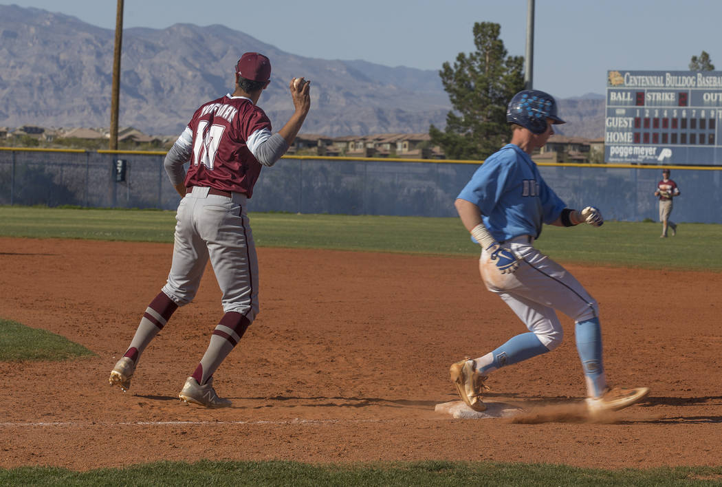 Cimarron-Memorial High School's Seth Hoffman (10) throws the ball as Centennial High School's Kian Wilbur (4) runs through first base in a game at Centennial High School in Las Vegas, Friday, Apri ...