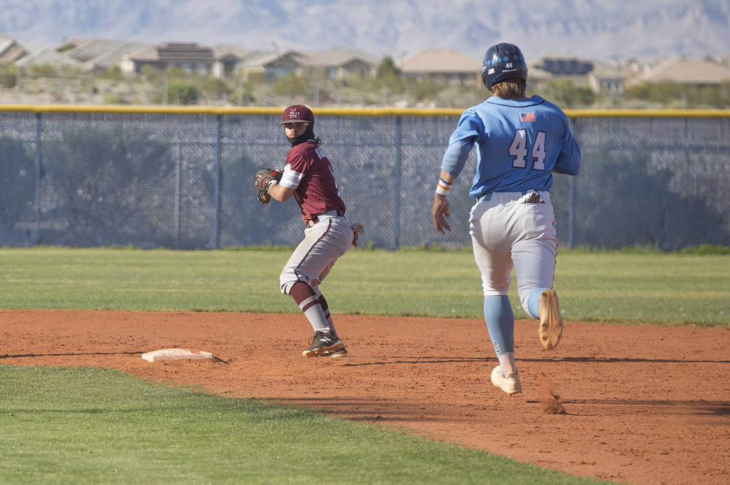 Cimarron-Memorial High School's Daniel Valdivia (1) prepares to throw the ball to a first baseman as Centennial High School's Kris Bow (44) runs to second in a game at Centennial High School in La ...