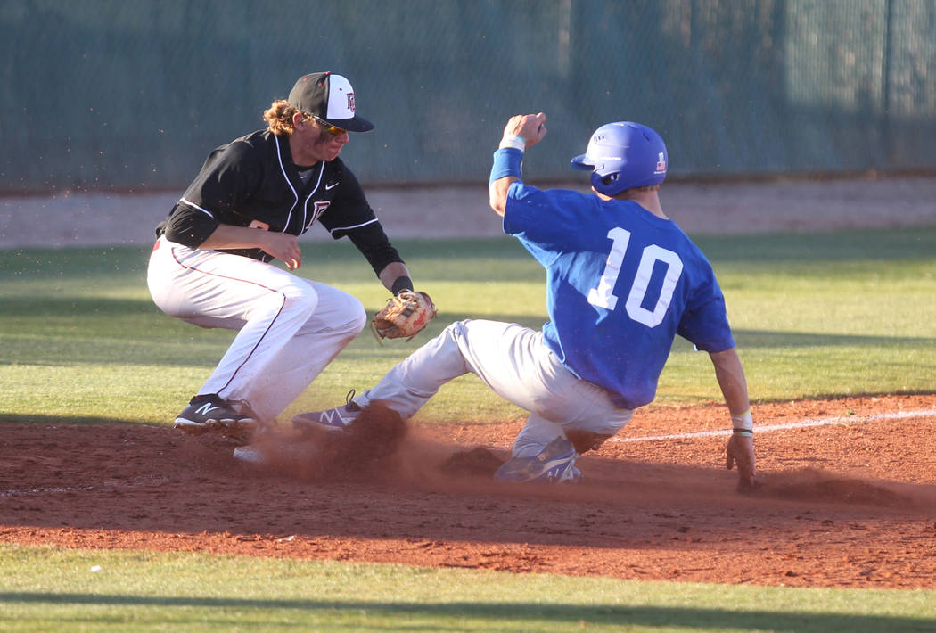 Green Valley baserunner Carter Gehlken (10) slides safely into third base under the tag of Zac Czerniawski of Desert Oasis at Desert Oasis High School in Las Vegas Thursday, March 8, 2018. K.M. Ca ...
