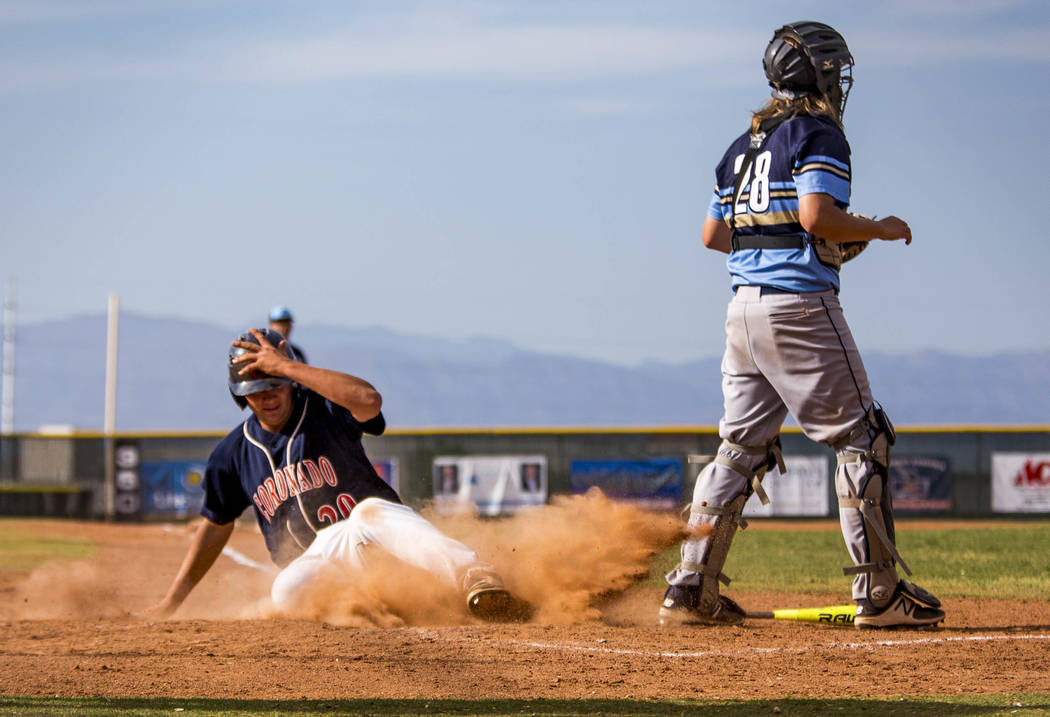 Coronado's Cristian Herrera slides in safe at home while Foothill catcher Eric Vaccaro stands by during the fourth inning at Coronado High School on Tuesday, April 24, 2018. Coronado won 12-2. Pa ...