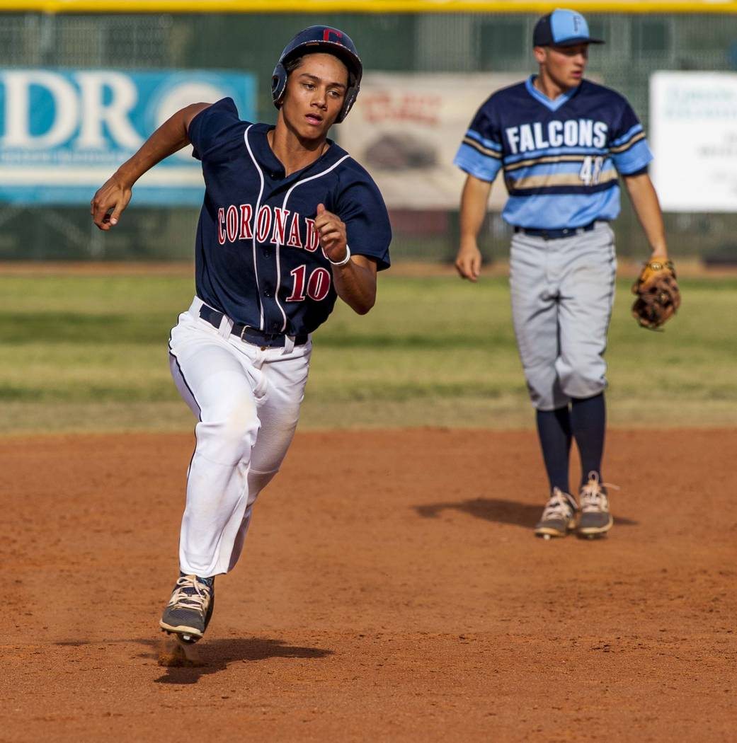 Coronado's Austin Gilmore runs toward third base while Foothill's Chayse Parenteau stands by in the background in the fifth inning at Coronado High School on Tuesday, April 24, 2018. Coronado won ...