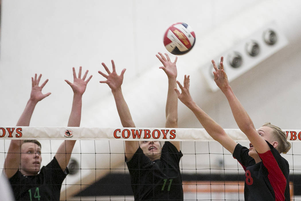 Las Vegas junior Shaun Kampshoff (8), right, attempts to hit the ball over the net as Palo Verde senior Josh Horn, left (14) and junior Stephen Banks (11), center block during the Class 4A state v ...
