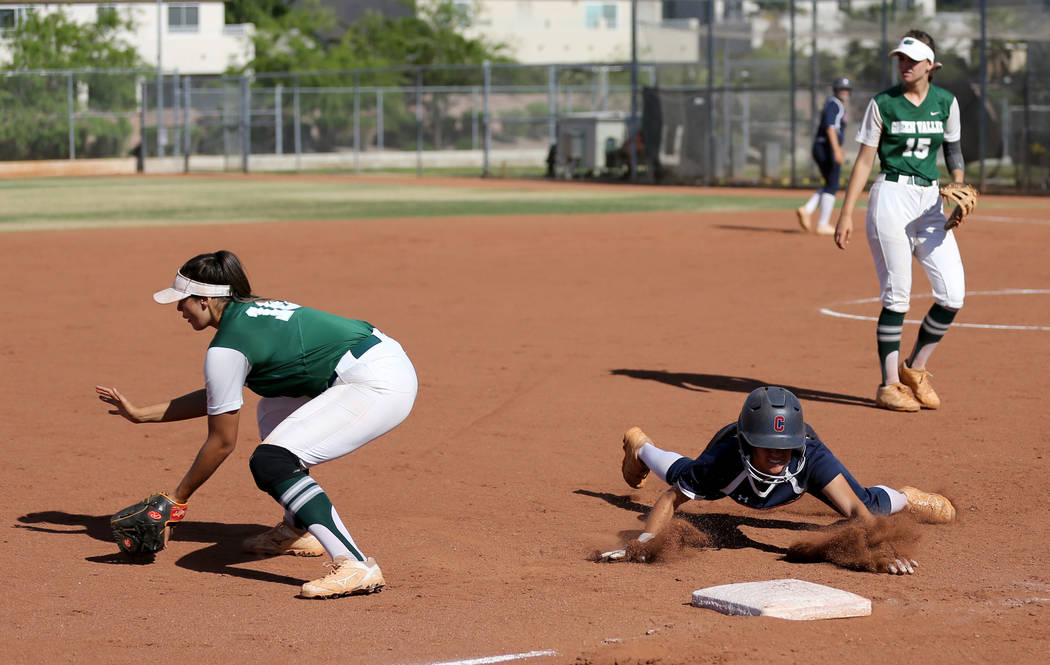 Coronado baserunner Aleah Baldonado (4) dives safely into third base as Green Valley infielder Cristina De Los Angeles (18) waits for the throw in the second inning of a softball game against Coro ...