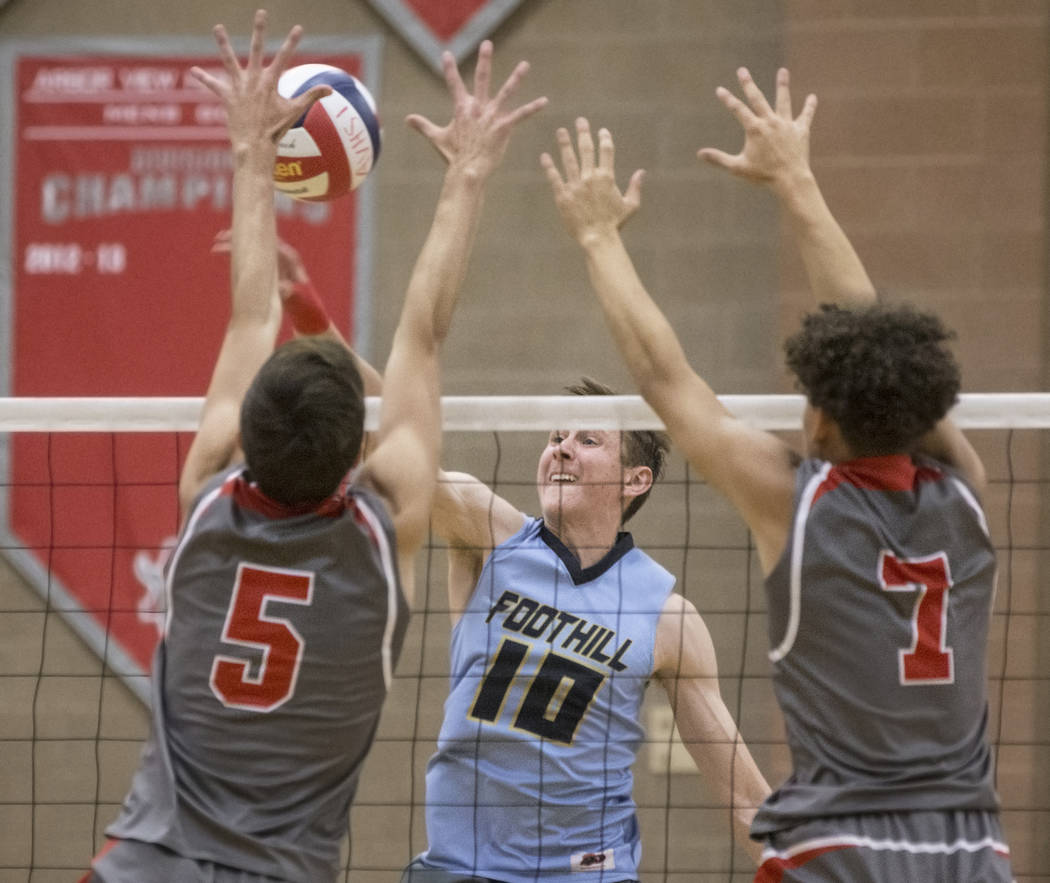 Foothills junior Caleb Stearman (10) makes a kill past Arbor View's Gideon Belnap (5) and Keandre Suares (7) during the class 4A state boys volleyball semifinal on Tuesday, May 15, 2018, at Arbor ...