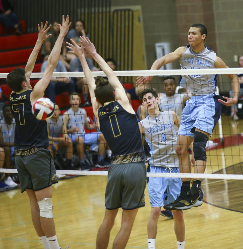 Centennial's Teon Taylor (13) spikes the ball between Foothill's Caden Thomas (7) and Dylan Meuller (1) during the second set of the Class 4A state volleyball championship match at Arbor View High ...
