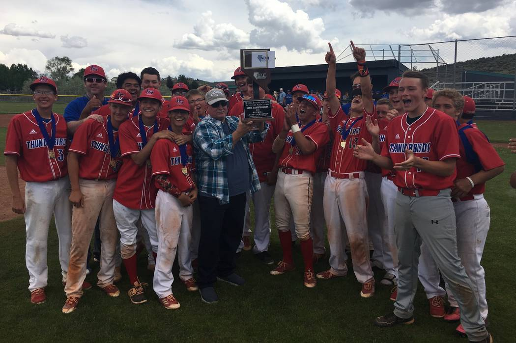 Indian Springs alumnus Donnie Hickman, center, poses with the Indian Springs baseball team holding the Class 1A state title trophy after a 12-2 victory over Pahranagat Valley on May 19, 2018 at No ...