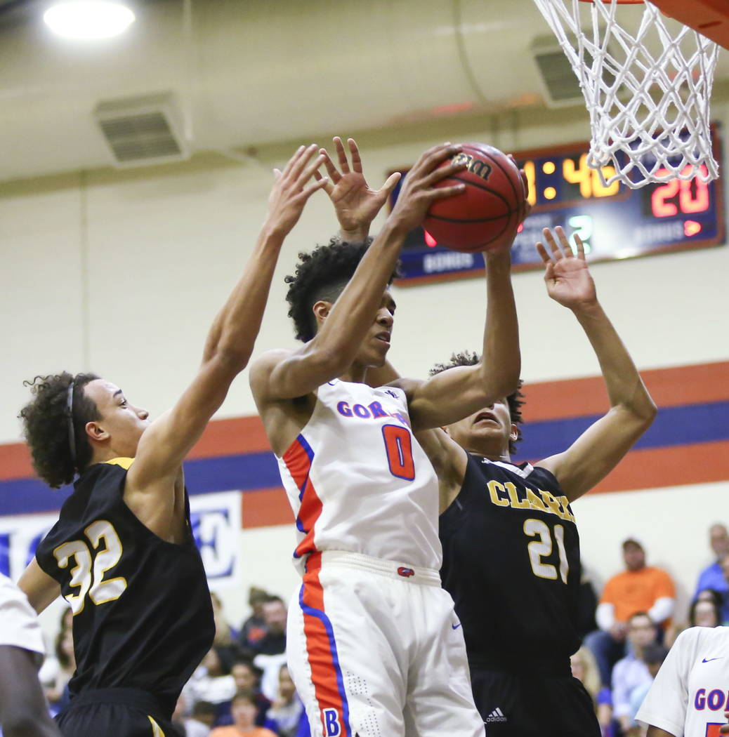 Bishop Gorman's Isaiah Cottrell (0) gets a rebound over Clark's Ian Alexander (32) and Jalen Hill (21) during a basketball game at Bishop Gorman High School in Las Vegas on Friday, Feb. 9, 2018. C ...