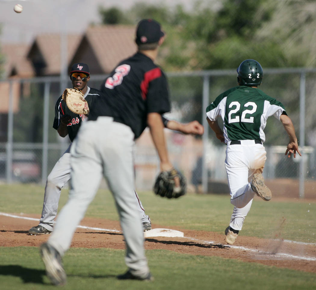 Las Vegas High School baseball player Bryan Harper throws to first baseman Marvin Campbell forcing out Rancho base runner Brandon Pletsch in the fifth inning of a game at Rancho High School Monday ...