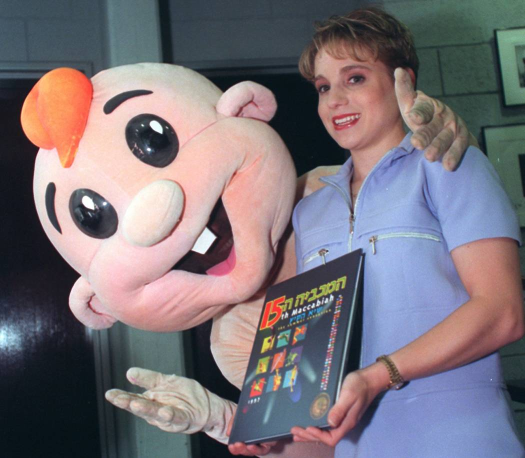 Olympic gold medalist Kerri Strug, right, poses with the mascot of Israel's Maccabiah Games in Tel Aviv Saturday July 12, 1997. Strug, who is on her first trip to Israel, will carry the torch to o ...