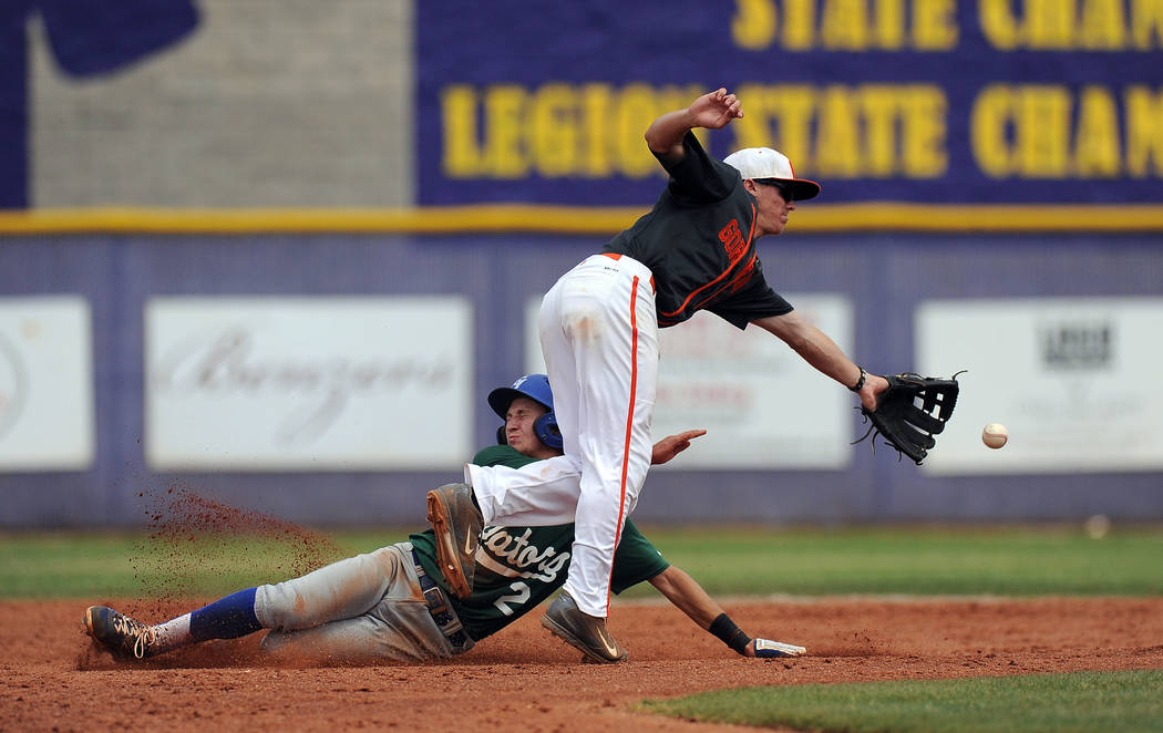 Bishop Gorman shortstop Cadyn Grenier, right, lunges to reach an off-target throw as Green Valley base runner Jarod Penniman (2) steals second base in the fifth inning of the NIAA Division I State ...