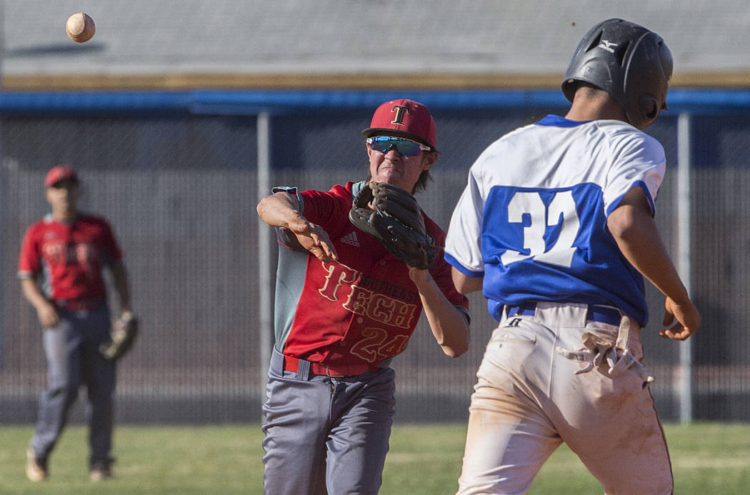 Southeast Career Tech sophomore second baseman Jason Collingbourne (24) turns a double play past Desert Pines senior Cesar Bailon (32) during the Roadrunners road matchup with the Jaguars on Tuesd ...