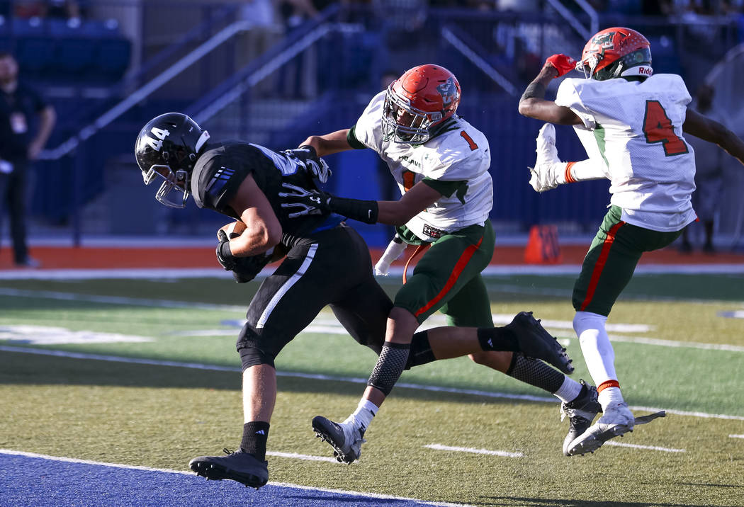 Desert Pines' Jesse Bravin (44) break past Mojave's Quincy Smith (4) and Desaun Smith (1) for a touchdown in the NIAA Class 3A state championship game at Bishop Gorman High School in Las Vegas on ...