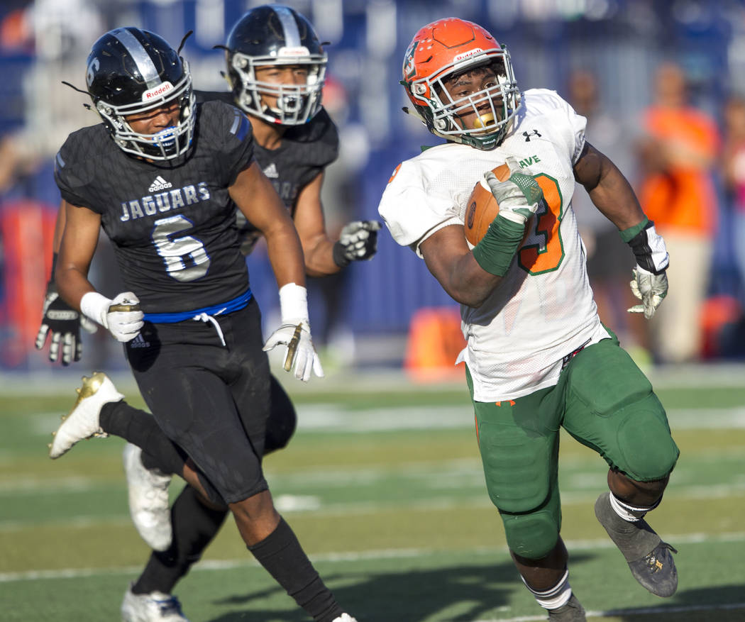 Mojave's Tawee Walker (3) outruns Desert Pines' Deaundre Newsome (6) for a touchdown during the NIAA Class 3A state championship game at Bishop Gorman High School in Las Vegas on Saturday, Nov. 25 ...