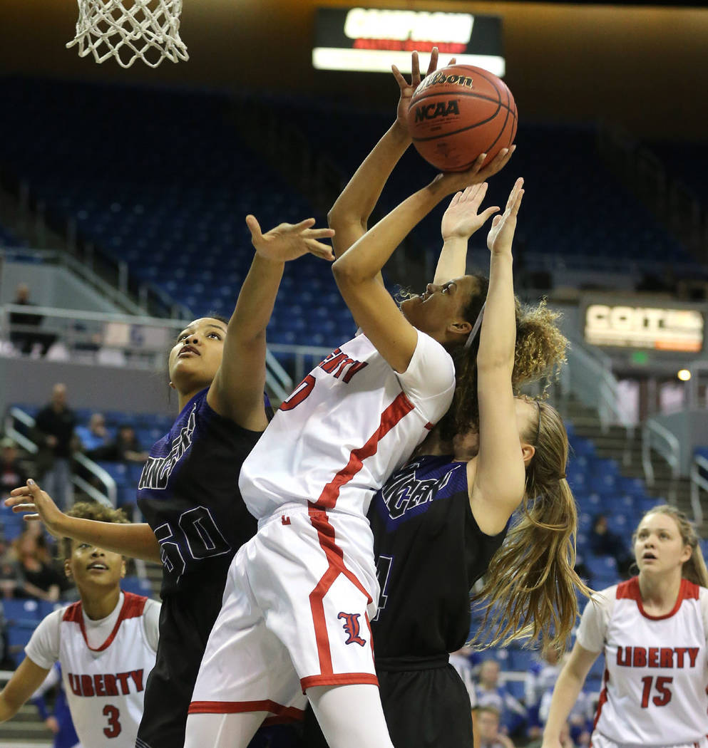 Liberty's Rae Burrell shoots past McQueen defenders Alisi Peaua and Kendra McAninch during the NIAA state basketball tournament in Reno, Nev. on Thursday, Feb. 22, 2018. Liberty defeated Mc ...