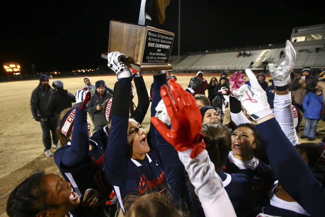 Coronado's Jensen Boman (18) raises the trophy while celebrating with teammates after defeating Shadow Ridge in the Class 4A state flag football championship game at Cimarron-Memorial High School ...