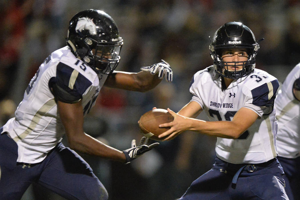 Shadow Ridge quarterback Kody Presser (33) hands the ball off to running back Malik Lindsey (15) during the Arbor View High School Shadow Ridge High School game at Arbor View in Las Vegas is seen ...