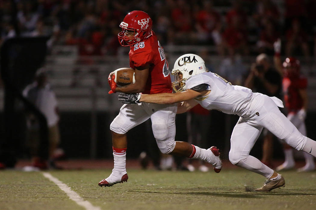Arbor View player Kyle Graham (25) attempts to run the ball as Faith Lutheran player Keagan Touchstone (9) tackles him during the first half of the game at Arbor View High School on Friday, Sept. ...