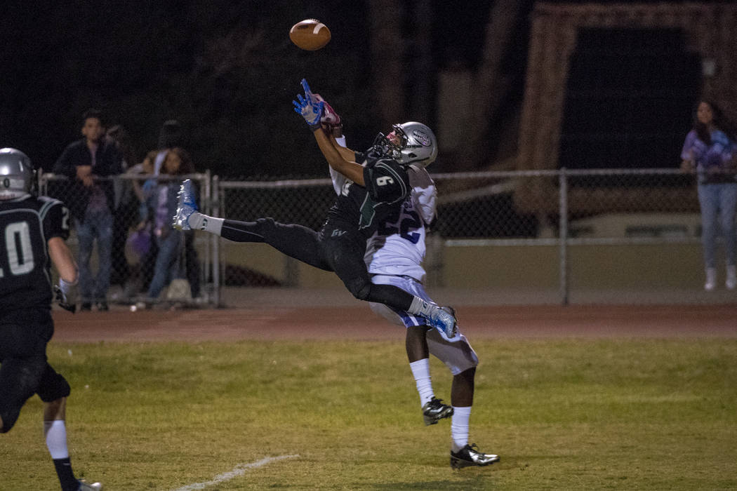Green Valley defensive back Antoin Kealoha (6) intercepts the ball in front of Silverado receiver Cameron Wiley (22) during the first half at Green Valley High School in Henderson on Friday, Oct. ...