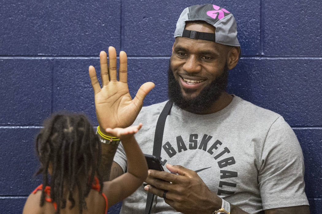 Los Angeles Lakers power forward LeBron James high fives his daughter Zhuri before the start of his son LeBron James Jr.'s Made Hoops Summer Showcase game on Wednesday, July 25, 2018, at Liberty H ...