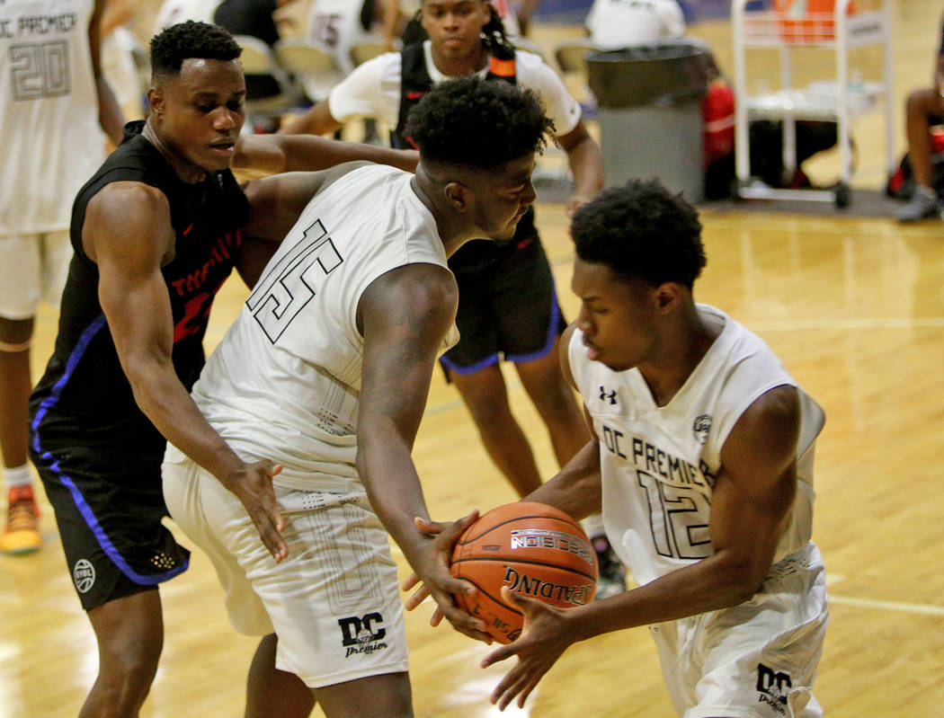 DC Premier's Makhi Mitchell (15) passes to his teammate Joshua Wallace (12) while blocking The Truth's Prince Gilliam (23) at the Fab 48 tournament at Bishop Gorman High School in Las Vegas, Sunda ...