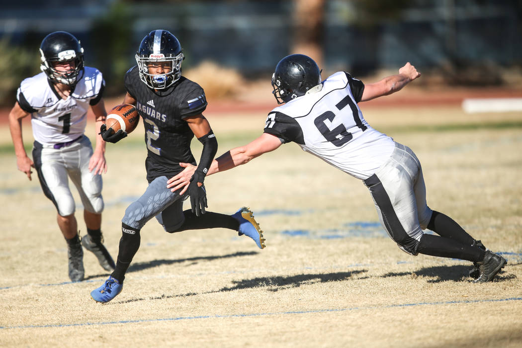 Desert Pines' Tye Moore (2), center, runs the ball past Spring Creek's Andrew Armstrong (67), right, during the second quarter of the Class 3A State football game at Desert Pines High School in La ...