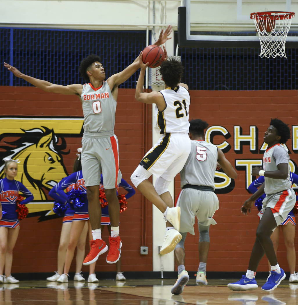 Clark's Jalen Hill (21) goes up to shoot as Bishop Gorman's Isaiah Cottrell (0) reaches out to block during a basketball game at Clark High School in Las Vegas on Tuesday, Jan. 30, 2018. Chase Ste ...