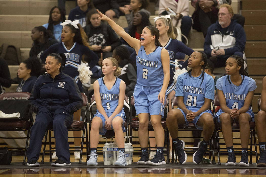 Centennial basketball player Melanie Isbell (2) stands to cheer on a teammate with Justice Ethridge (21) sitting to her right during a game against Cimarron-Memorial at Cimarron-Memorial High Sch ...