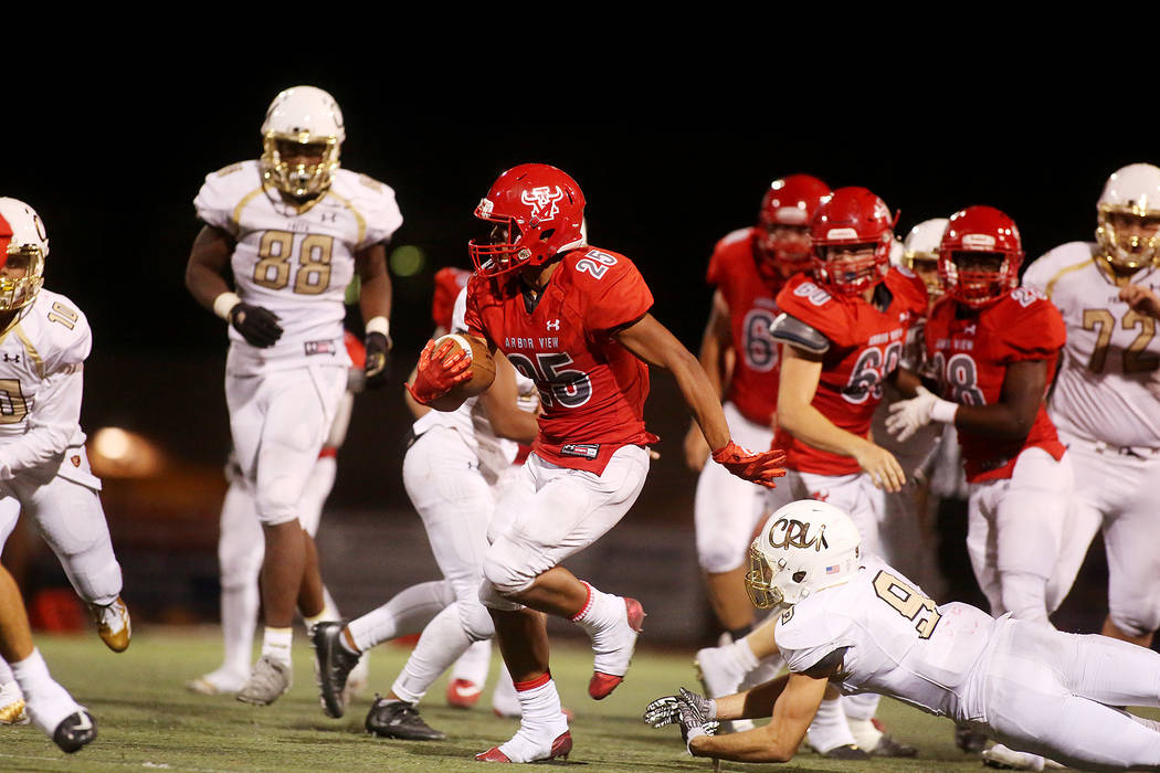 Arbor View player Kyle Graham run the ball as Faith Lutheran attempts to tackle during the second half of the game at Arbor View High School on Friday, Sept. 15, 2017, in Las Vegas. Arbor View wo ...