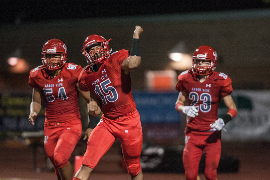 Arbor View Aggie linebacker Billy Davis (15) celebrates a touchdown with his teammates Tai Tuinei (54) and Deago Stubbs (23) at Arbor View High School on Friday, Sep. 1, 2017, in Las Vegas. Morgan ...