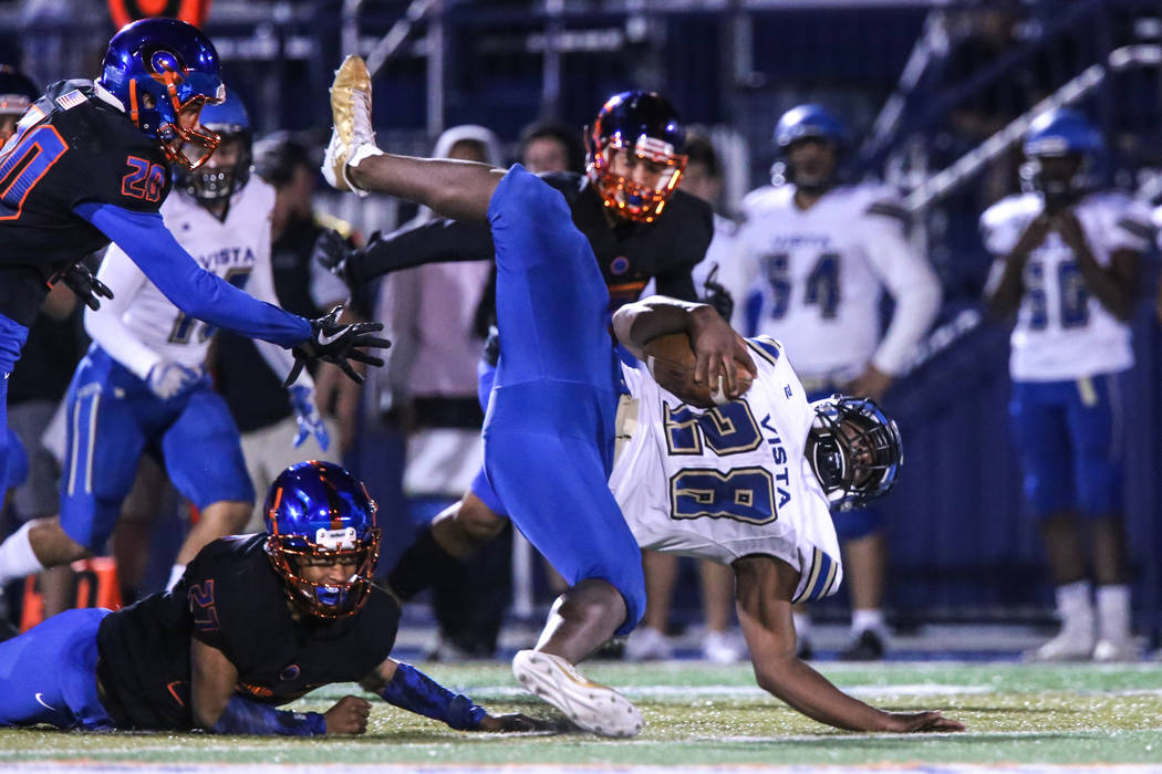 Sierra Vista's Bryan Lagrange (28), right, falls during a play against Bishop Gorman during the fourth quarter of a football game at Bishop Gorman High School in Las Vegas, Thursday, Oct. 26, 2017 ...