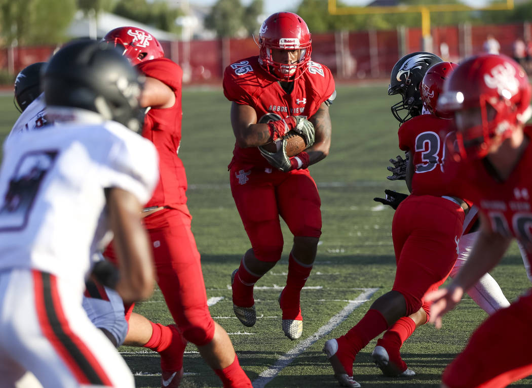 Arbor View Aggies running back Kyle Graham (25) carries the ball through Valley View Eagles defenders for a touchdown during the first half of a varsity football game at Arbor View High School in ...