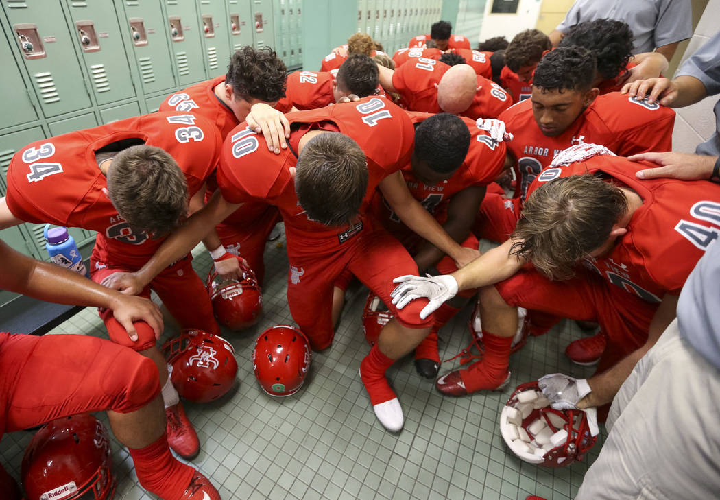 The Arbor View Aggies kneel in prayer in their locker room before playing the Valley View Eagles of California in a varsity football game at Arbor View High School in Las Vegas on Friday, Aug. 17, ...