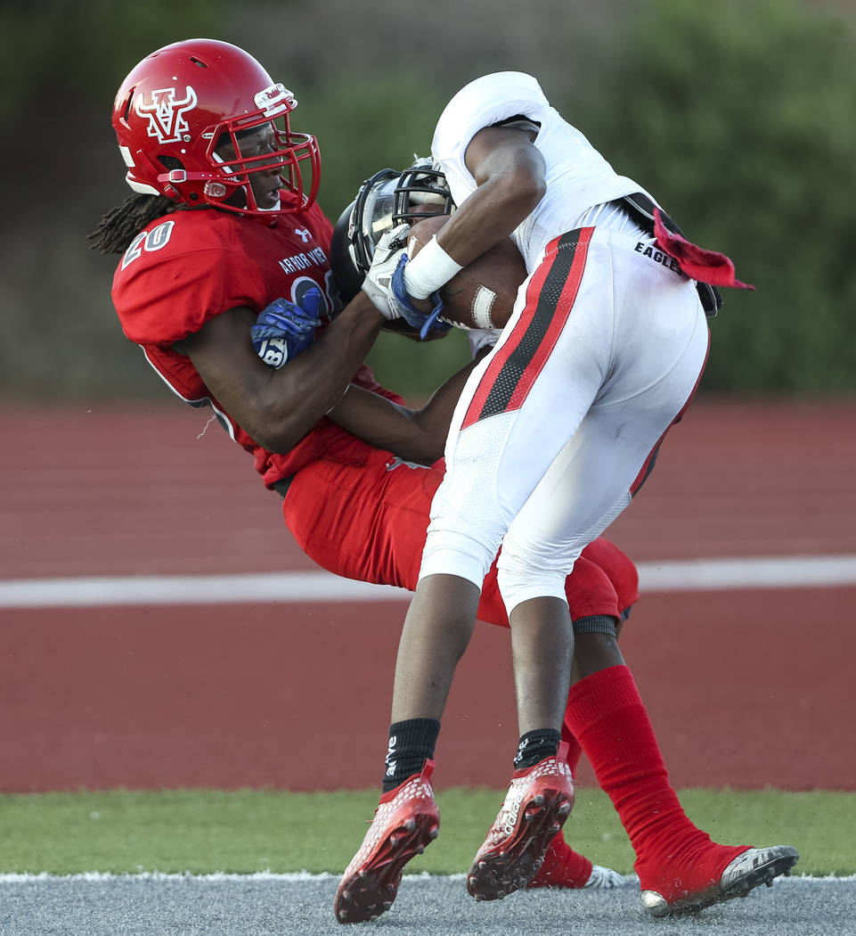 Arbor View Aggies cornerback Rickie Davis Jr. (20), left, brings down Valley View Eagles wide receiver Sean Norwood (1) as he scores a touchdown during the first half of a varsity football game at ...