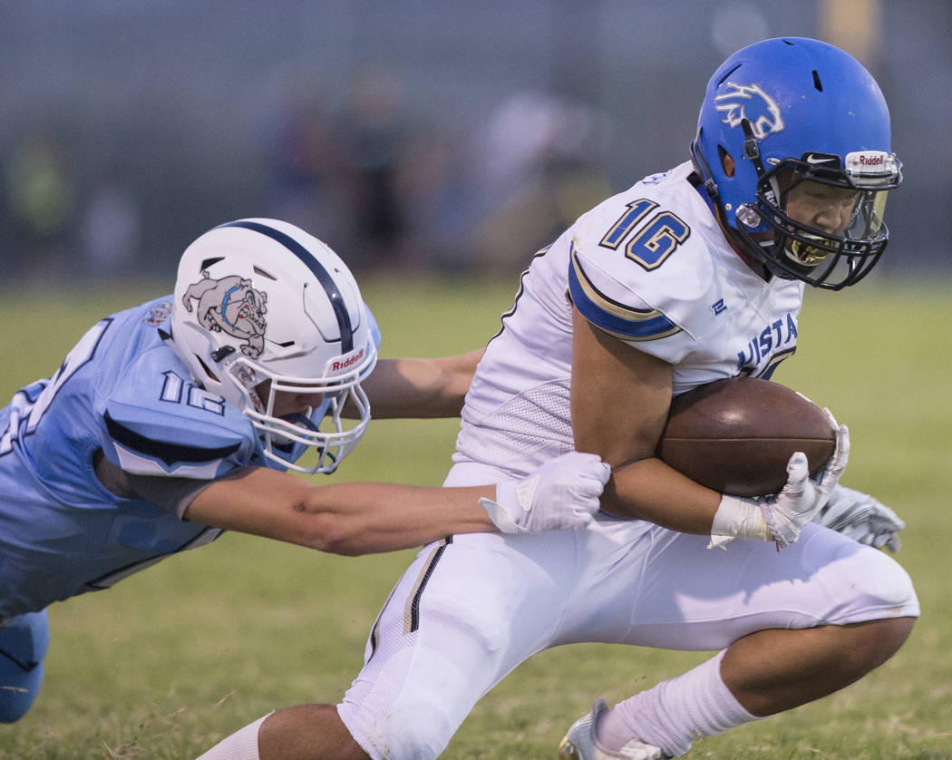 Sierra Vista senior wide receiver Tristen Jimenez (16) fights for yardage with Centennial senior defensive back Tyler Hermanson (12) in the first quarter on Friday, Aug. 17, 2018, at Centennial Hi ...