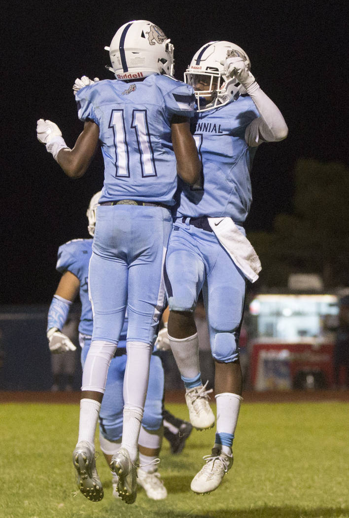 Centennial junior running back Jordan Smith (1) and wide receiver Amari Miller (11) celebrate after the Bulldogs pulled ahead in the fourth quarter against Sierra Vista High School on Friday, Aug. ...