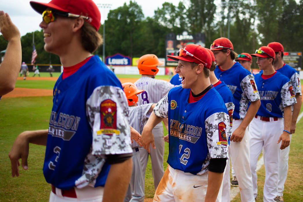 Logan LaCourse of Midland, Mich., Berryhill Post 165 laughs as he high fives a batboy after the team took down Las Vegas Post 40 3-2 in game seven of The American Legion World Series at Veterans F ...