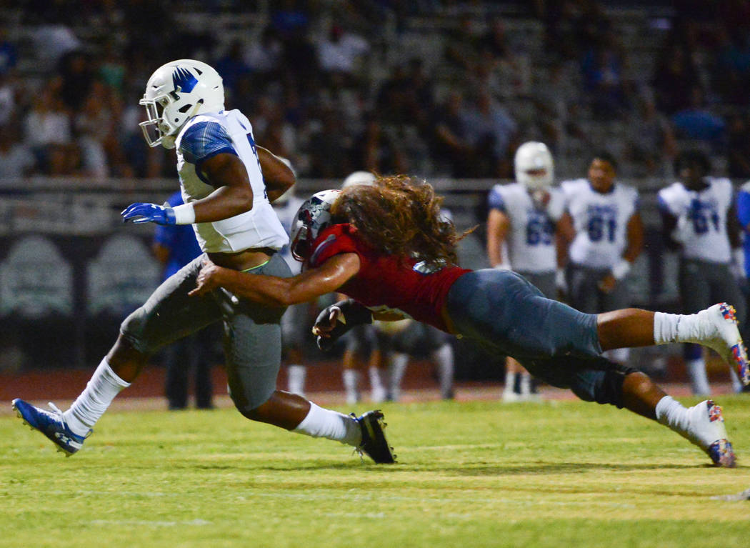 IMG Academy running back Noah Cain (7) breaks a tackle from Liberty's Zyrus Fiaseu (30) at Liberty High School in Henderson on Friday, Sept. 7, 2018. IMG Academy leads at halftime 21-0. Brett Le B ...
