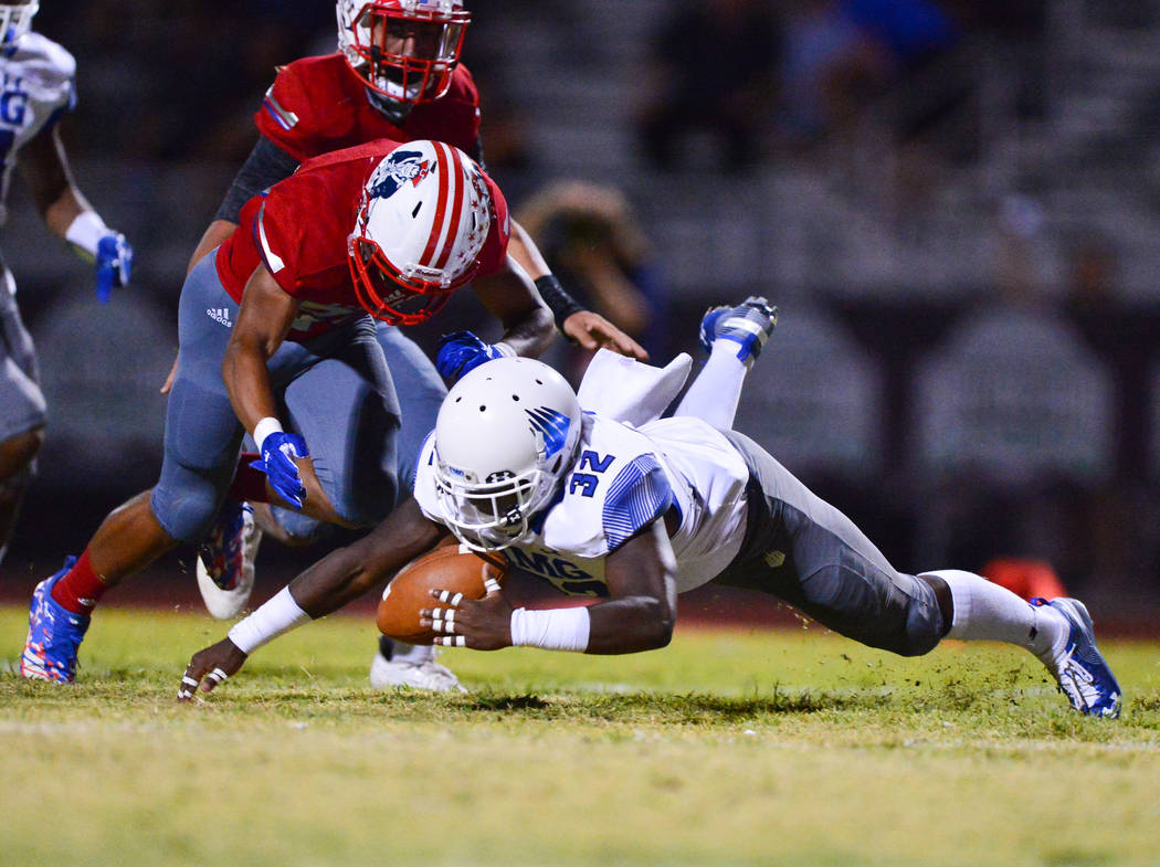 IMG Academy kick returner Chandler Mcgruder (32) recovers a muffed punt under Liberty defensive back Isiah Revis (20) at Liberty High School in Henderson on Friday, Sept. 7, 2018. IMG Academy lead ...