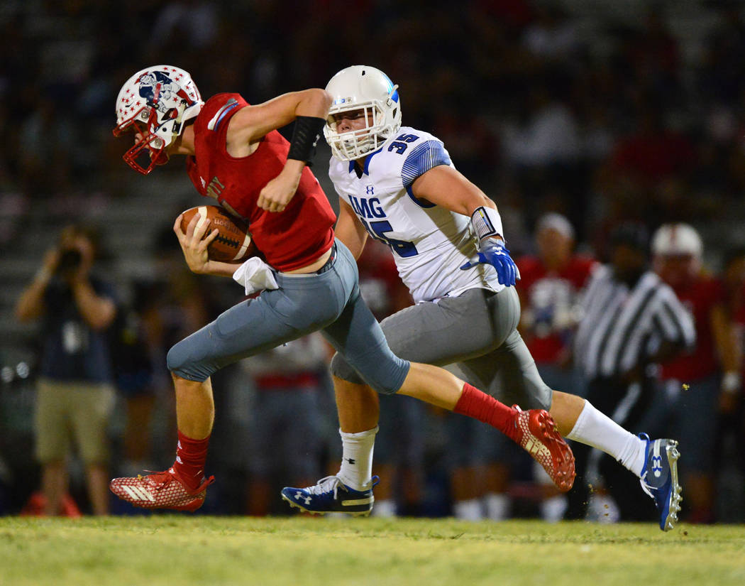Liberty quarterback Kanyon Stoneking (7) is chased by IMG Academy's Bruce Seton III (35) during a game at Liberty High School in Henderson on Friday, Sept. 7, 2018. IMG Academy won 35-0. Brett Le ...