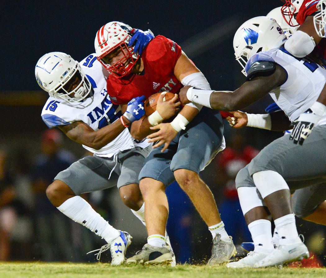 Liberty's Kyle Beaudry (4) is tackled by IMG Academy defenseman Jayden Curry (15) during a game at Liberty High School in Henderson on Friday, Sept. 7, 2018. IMG Academy won 35-0. Brett Le Blanc L ...
