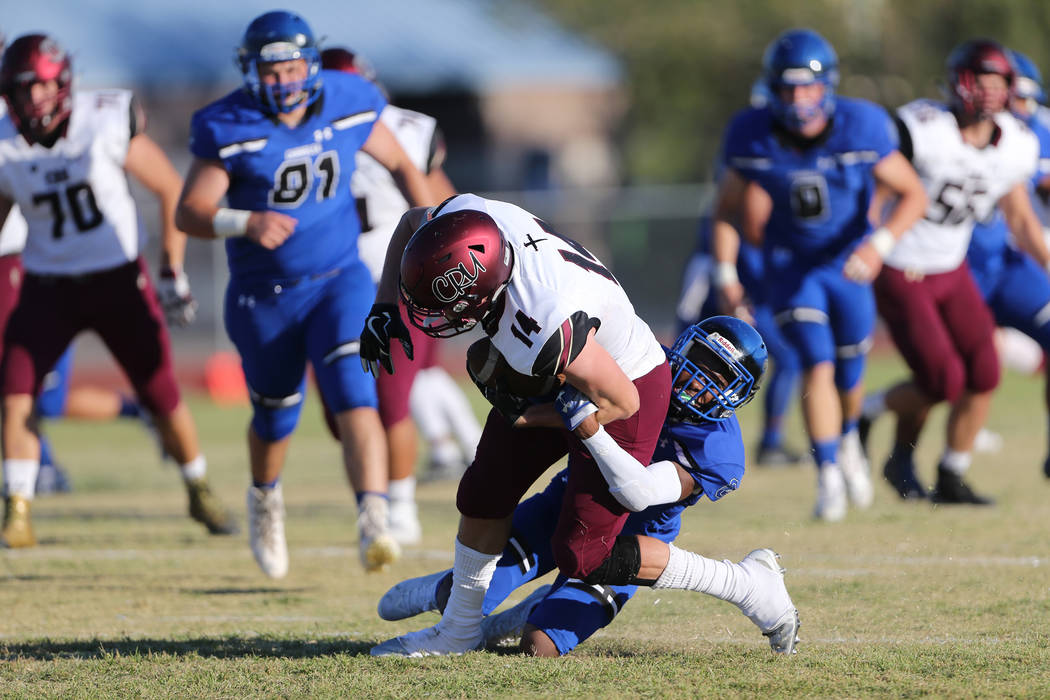 Faith Lutheran's Peyton Thornton (14) is tackled against Chandler's Latrell Tellis (29) in the second quarter of a football game at Liberty High School in Henderson, Saturday, Sept. 8, 2018. Erik ...