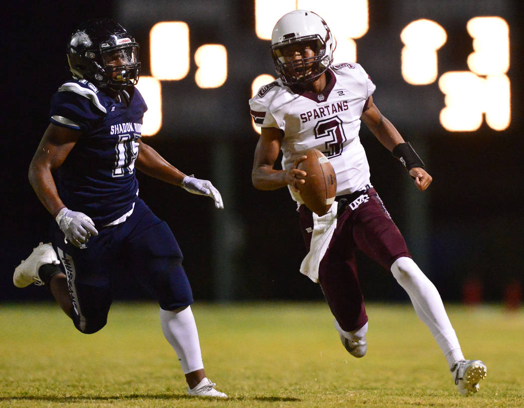 Cimarron-Memorial quarterback Branden Smith (3) is chased down by Shadow Ridge defensive end Isaiah Tucker (15) during a game at Shadow Ridge High School in Las Vegas on Friday, Sept. 14, 2018. Br ...