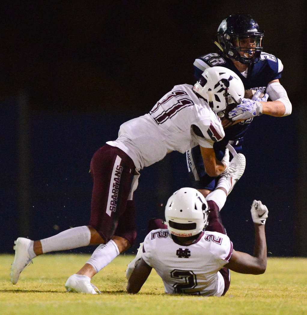 Shadow Ridge running back Brock Weisheim (28) is tackled by Cimarron Memorial's Jose Carrasco (11) during a game at Shadow Ridge High School in Las Vegas on Friday, Sept. 14, 2018. Brett Le Blanc/ ...