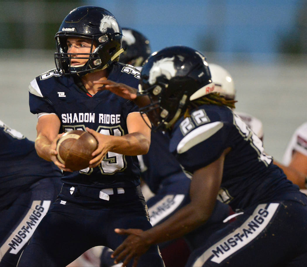 Shadow Ridge quarterback Kody Presser (33) hands the ball off to running back Anthony Wheaton (22) during a game against Cimarron-Memorial at Shadow Ridge High School in Las Vegas on Friday, Sept. ...