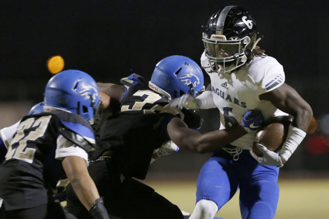 Desert Pines' Cameron Wiley (6) keeps a ball away from Sierra Vista's Javaris Andrews, center, and Josiah Antolin (22) during the first half of a football game at Sierra Vista High School in Las V ...