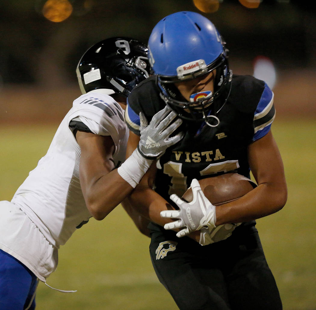 Sierra Vista's Jordan Solomon, right, is tackled by Desert Pines' Corey Clark, left, during the second half of a football game at Sierra Vista High School in Las Vegas, Friday, Sept. 14, 2018. Chi ...